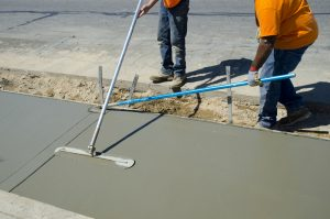 Workers laying concrete for a foundation in Johnson City